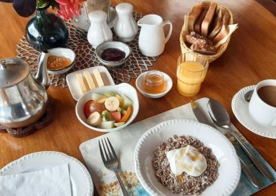 Wooden table is laid with toast, tea, jams, butter and milk. There is a bowl of muesli topped with yogurt and honey and a bowl of fresh fruit