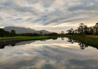 Clouds reflect in a still lake surrounded by manicured greens. There is a ruined castle and mountains in the background