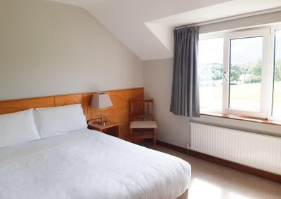 A double bed with white linen and a large window with views of fields, trees and mountains