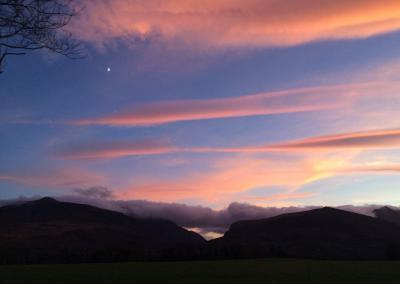 Vibrant pink clouds contrast against the dark blue skies and silhouette of the Gap of Dunloe. A half moon is shining in the sky