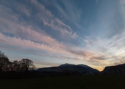 Pastel blue and pink skies and wispy winter clouds over the silhouette of the Gap