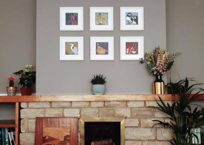 Six colourful lino prints above the fireplace surrounded by plants and cut flowers