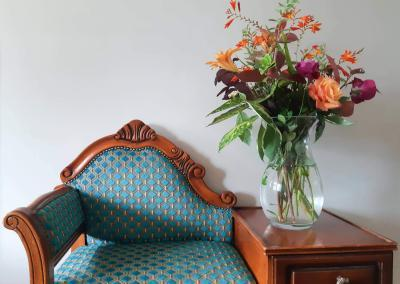 A large glass vase sits next to a small wooden decorative chair. In it are lovely orange and pink flowers and green foliage