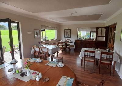 Four wooden tables are set for breakfast with views of green fields outside