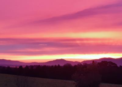Vivid pink, purple and orange skies against the shadows of the Killarney mountains