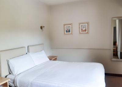 A double bed with white linen and two pictures of flowers in vases on the wall