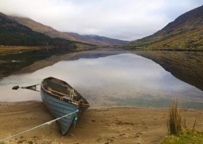 A blue boat sits on the shore of a mirror-like lake with mountains reflected in the background