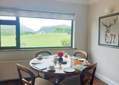 A round wooden table is laid with a bright red rose in a vase. There is a painting of a stag and a view of cows and the Gap of Dunloe out of the window