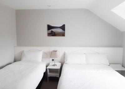 A single and double bed with white linen and a photograph of the wall of 'the boat on Lough Cummeenduff'.