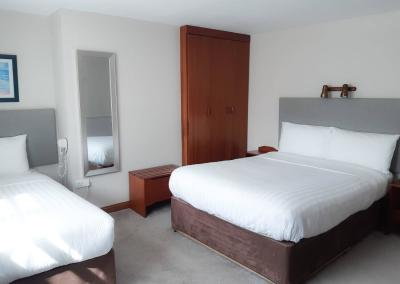 A double and single bed with white linen in a light and airy room