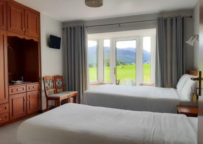 A double a single bed with white linen and views of the fields, mountains and louie, the Corgi, outside.
