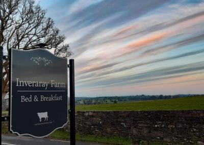"""Dark grey sign with silver letters and the silhouette of a cow saying """"Inveraray Farm Bed & Breakfast"""""""