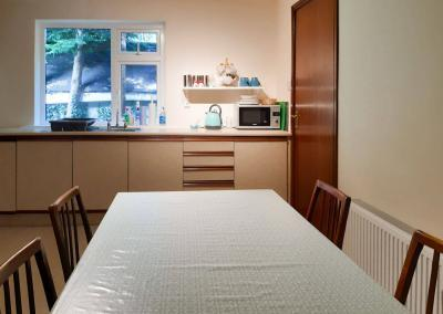 Dining table and 4 chairs with kitchen units in the background with blue mugs, a blue kettle and a microwave.