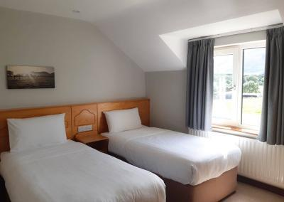 Two single beds with white linen and a view of fields and trees out of the window.