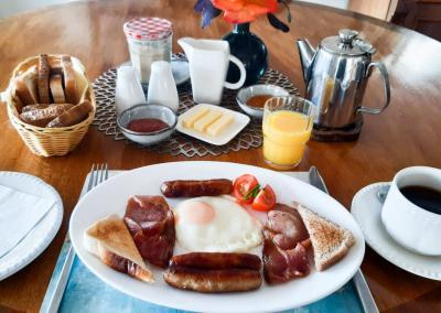 Table is set with toast, orange juice, coffee, butter and jam. In the centre is a plate of bacon, sausages, tomato and a fried egg.