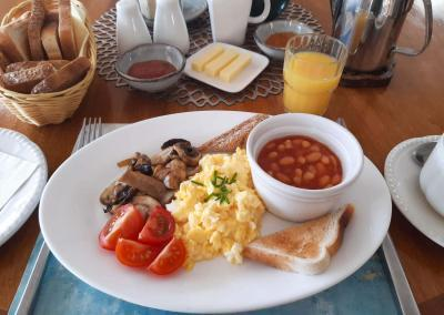 Table is set with toast, orange juice, coffee, butter and jam. In the centre is a plate of scrambled egg, baked beans, mushrooms and tomato